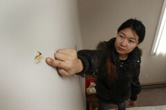 Kate Cheng points to a bullet hole in her apartment.