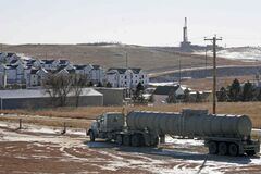 In this Wednesday, Feb. 26, 2014 photo, an oil truck sits in a dirt lot near a new housing development in Watford City, N.D. The housing development is part of the towns growth explosion from the Bakken oil boom.