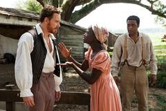 This image released by Fox Searchlight shows Michael Fassbender, left, Lupita Nyong'o and Chiwetel Ejiofor, right, in a scene from the film,