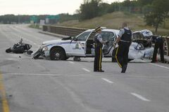 RCMP officers investigate a collision involving an RCMP cruiser car and a motorcycle in the southbound lanes of Highway 59 on the north Floodway bridge on Sunday.