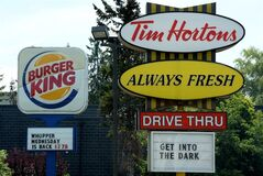A Burger King sign and a Tim Hortons sign are displayed on St. Laurent Boulevard in Ottawa on Monday, August 25, 2014. Canada's iconic coffee chain Tim Hortons and Miami-based Burger King say they will join forces, but will operate as independent brands to form the world's third-largest quick service restaurant company. THE CANADIAN PRESS/Sean Kilpatrick
