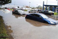 Flooded vehicles sit in water following flash flooding in Kamloops, B.C., on Wednesday, July 23, 2014. A cell of torrential rain caused flash flooding in Kamloops turning roads into rivers, creating immediate small lakes and flooding numerous basements. THE CANADIAN PRESS/Kamloops This Week, Andrea Klassen