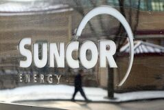 A pedestrian is reflected in a Suncor Energy sign in Calgary, Feb. 1, 2010. THE CANADIAN PRESS/Jeff McIntosh