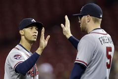 Atlanta Braves shortstop Andrelton Simmons, left, is congratulated by first baseman Freddie Freeman (5) after they defeated the Cincinnati Reds 8-0 in a baseball game, Thursday, Aug. 21, 2014, in Cincinnati. Simmons had a home run and two RBIs in the game. (AP Photo/Al Behrman)