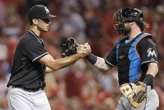 Miami Marlins relief pitcher Steve Cishek, left, is congratulated by catcher Jarrod Saltalamacchia after the Marlins defeated the Cincinnati Reds 4-3 in a baseball game, Saturday, Aug. 9, 2014, in Cincinnati. Cishek earned his 29th save. (AP Photo/Al Behrman)