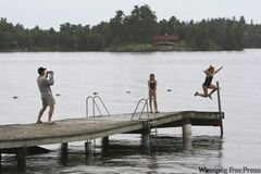 Jim Ludlow takes a photo in 2009 of his daughter Fiona jumping off the dock at Coney Island into the waters of Lake of the Woods while friend Nicole Brownlee looks on.