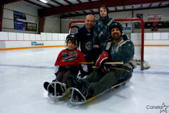Sherwood Armbruster (back left) and Glenelm physical education teacher Errol Sookram (front right) helped organize a sledge hockey lesson for Grade 4 and 5 students at the school at Gateway Recreation Centre on Feb. 20. Armbruster's sons Luke (front left) and Isaiah (back right) both play sledge hockey for the Manitoba Sledgehammers.