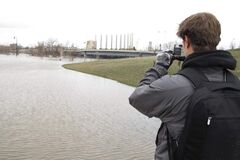 Spencer McCombs, a student at Concordia College in Moorhead, Minn., takes photographs of the Red River Wednesday. The National Weather Service reported that the river appears to have crested. McCombs is doing a research project on flooding.