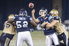 Toronto Argonauts quarter back Rickie Ray (centre right) makes a pass despite being tackled by Winnipeg Blue Bombers Greg Peach during first half CFL football action in Toronto on Tuesday.