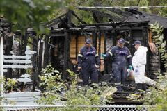 Investigators inspect the charred shell of a home in Winnipeg Beach where two people died and one was sent to a Winnipeg hospital after a fire early Sunday morning.