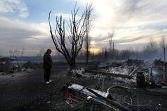 Werner Wersh looks at the piles of burning rubble that remain of his neighbour's homestead near Teulon after a grass fire got out of control and burned down the house, barn, RV and workshop on Friday.