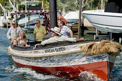 In this April 12, 2012, photo provided by the Florida Keys News Bureau, the African Queen, the original vessel from the classic 1951 movie by the same name, sails on a Key Largo, Fla., canal steered by Stephen Bogart, center, son of Humphrey Bogart, who starred in the film. Stephen Bogart is to host the Bogart Film Festival, set for May 2-5, 2013, in Key Largo. Built in 1912, the 30-foot boat was refurbished to provide Florida Keys visitors an opportunity to ride the cinema icon. (AP Photo/Florida Keys News Bureau, Andy Newman)