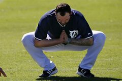 Detroit Tigers pitcher Joba Chamberlain stretches during the team's first day of baseball spring training for pitchers and catchers, in Lakeland, Fla., Friday, Feb. 14, 2014. (AP Photo/Gene J. Puskar)