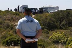 Portuguese Republican Guard policemen and other officers stand guard in a cordoned-off area, in Praia da Luz, Lagos, southern Portugal, Monday, June 2, 2014. Police investigating the disappearance of Madeleine McCann cordoned off Monday an area of scrubland near where the British girl vanished seven years ago. Officers placed yellow-and-white police tape around the waste ground, which is mostly level and slightly larger than a soccer field, and were expected to conduct a forensic examination of the area in the coming days. (AP Photo/Francisco Seco)
