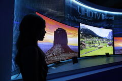 IA model stands next to a display of Samsung's curved 4K UHD TVs during a preview event at the International Consumer Electronics Show in Las Vegas on Sunday, Jan. 5, 2014.