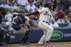 Atlanta Braves' Tommy La Stella San hits in Andrelton Simmons on a single to center field as San Diego Padres catcher Rene Rivera (44) watches during the third inning of a baseball game, Sunday, July 27, 2014, in Atlanta. (AP Photo/John Amis)