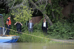 Winnipeg Police Service investigators watch as divers from the Underwater Search and Recovery Unit search the Assiniboine River for Lisa Gibson. Gibson has been missing since Wednesday morning when her two kids, Anna and Nicholas, were found unresponsive in the family home in Westwood. The children were rushed to hospital but did not survive.