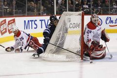 Washington Capitals' Matt Hendricks (26) checks Winnipeg Jets' Nik Antropov (80) as he pushes the puck out front of the net of Washington Capitals goaltender Tomas Vokoun (29) during second-period NHL action in Winnipeg on Friday.