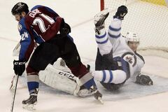 Winnipeg Jets centre Jim Slater is called for interfering with the goalie while Colorado Avalanche right-winger Marc-Andre Cliche clears the puck during the first period of an NHL game at Pepsi Center in Denver, Colo., Monday.