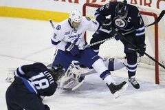 Winnipeg Jets forward Bryan Little (18) blows a shot past teammate Andrew Ladd, Tampa Bay Lightning defenceman Eric Brewer and goaltender Cedrick Desjardins during the first period of an NHL game at the MTS Centre on Sunday. The Jets held on to win 3-2.