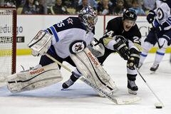 Pittsburgh Penguins left wing Matt Cooke (24) reaches for the puck in front of Winnipeg Jets goalie Al Montoya (35) during the second period of an NHL hockey game in Pittsburgh, Thursday.