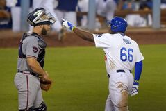 Los Angeles Dodgers' Yasiel Puig, right gestures after hitting a solo home run, next to Atlanta Braves catcher Evan Gattis during the third inning of a baseball game, Thursday, July 31, 2014, in Los Angeles. (AP Photo/Mark J. Terrill)