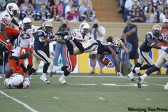 Winnipeg Blue Bombers Jonathan Hefney (23) leaps for some extra yards against the B.C. Lions in the first half of CFL action in Winnipeg Thursday.