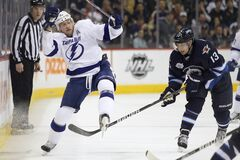 Tampa Bay Lightning's Steven Stamkos (91) is upended by Winnipeg Jets' Kyle Wellwood (13) during first-period NHL action in Winnipeg on Thursday.