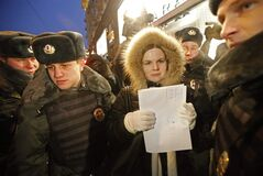 Police officers detain a protester near the State Duma, in Moscow, Russia, Wednesday, Dec. 19, 2012. People picket parliament's lower chamber, which is set to debate an amendment that would ban Americans from adopting Russian children. (AP Photo/Misha Japaridze)