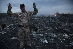 A man gestures at a crash site of a passenger plane near the village of Grabovo, Ukraine, Thursday, July 17, 2014. Ukraine said a passenger plane carrying 295 people was shot down Thursday as it flew over the country, and both the government and the pro-Russia separatists fighting in the region denied any responsibility for downing the plane. (AP Photo/Dmitry Lovetsky)