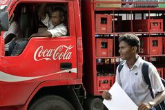 FILE - In this June 26, 2012 file photo, a man walks past a truck that distributes Coca Cola in Mumbai, India. An increasing thirst for Coca-Cola products in China, India and the Middle East helped boost the company's international sales by 3 percent in the second quarter while volume remained flat in North America. (AP Photo/Rajanish Kakade, File)