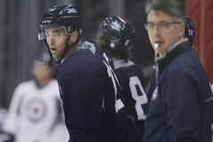 Winnipeg Jets coach Claude Noel (right) and captain Andrew Ladd watch the action on Day 2 of training camp on Monday at the MTS Centre. Noel has less than a week to put together his lines.
