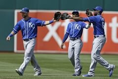 From left, Kansas City Royals outfielders Alex Gordon, Jarrod Dyson, and Lorenzo Cain celebrate the 4-2 defeat of the Oakland Athletics at the end of a baseball game Sunday, Aug. 3, 2014, in Oakland, Calif. (AP Photo/Ben Margot)