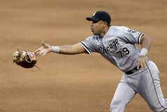 Chicago White Sox's Jose Abreu tosses his glove with the ball to starting pitcher Scott Carroll to get Cleveland Indians' Lonnie Chisenhall out at first base in the sixth inning of a baseball game, Saturday, May 3, 2014, in Cleveland. Chisenhall was out. (AP Photo/Tony Dejak)