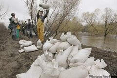 Volunteers sandbag on the southern dike of the Assiniboine River in Brandon on Monday. The high water levels of the Assiniboine River are threatening surrounding communities.