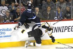 Winnipeg Jets forward Evander Kane gets upended by Boston Bruins defenceman Johnny Boychuk during first-period NHL action at the MTS Centre Tuesday.
