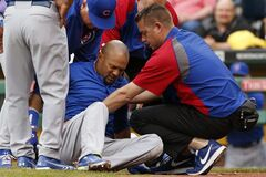 Chicago Cubs' Emilio Bonifacio is helped up by a team trainer and manager Rick Renteria, top left, during the first inning of a baseball game against the Pittsburgh Pirates in Pittsburgh Thursday, June 12, 2014. Bonifacio was helped to the dugout and did not remain in the game. The nature of his injury is not known at this time. (AP Photo/Gene J. Puskar)