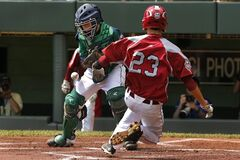 Lynnwood's Colton Walsh (23) scores as the ball gets away from Rapid City catcher Mason Litz during the first inning of a baseball game at the Little League World Series tournament in South Williamsport, Pa., Saturday, Aug. 16, 2014. (AP Photo/Gene J. Puskar)