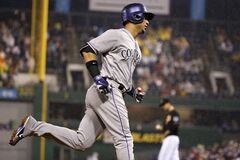 Colorado Rockies' Carlos Gonzalez, left rounds third after hitting a two run home run off Pittsburgh Pirates starting pitcher Charlie Morton, right rear, during the seventh inning of a baseball game in Pittsburgh Saturday, July 19, 2014. (AP Photo/Gene J. Puskar)