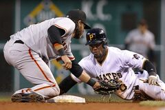 Pittsburgh Pirates' Starling Marte, right, slides safely around the tag of San Francisco Giants shortstop Brandon Crawford, left, with a stolen base during the third inning of a baseball game in Pittsburgh Monday, May 5, 2014. Giants manager Bruce Bochy called for a replay and the safe call was upheld. (AP Photo/Gene J. Puskar)