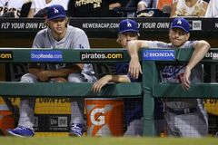 Los Angeles Dodgers starting pitchers Clayton Kershaw, left, and Zack Greinke, center, and catcher A.J. Ellis watch from the dugout during the ninth inning of a 6-1 loss to the Pittsburgh Pirates in a baseball game in Pittsburgh, Wednesday, July 23, 2014. (AP Photo)