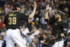 Pittsburgh Pirates closer Jason Grilli (39) celebrates with catcher Russell Martin after getting the save in a 4-3 Pirates win over the Washington Nationals in a baseball game in Pittsburgh, Friday, May 23, 2014. (AP Photo/Gene J. Puskar)