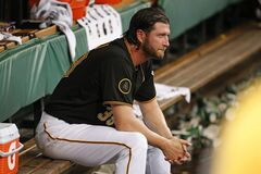 Pittsburgh Pirates relief pitcher Jason Grilli sits in the dugout after giving up a solo home run to Cincinnati Reds' Devin Mesoraco during the ninth inning of a baseball game in Pittsburgh, Thursday, June 19, 2014. The Pirates won 4-3 in 12 innings. (AP Photo/Gene J. Puskar)