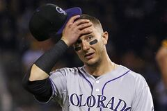 Colorado Rockies shortstop Troy Tulowitzki reacts to Pittsburgh Pirates' Starling Marte being hit in the head by a pitch from Rockies relief pitcher Adam Ottavino during the seventh inning of a baseball game in Pittsburgh on Friday, July 18, 2014. The Pirates won 4-2. (AP Photo/Gene J. Puskar)