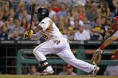 Pittsburgh Pirates' Josh Harrison (5) drives in a run with a single off Cincinnati Reds relief pitcher Sam LeCure during the seventh inning of a baseball game in Pittsburgh Tuesday, June 17, 2014. (AP Photo/Gene J. Puskar)