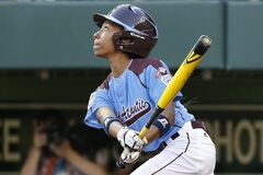 Philadelphia's Mo'ne Davis drives in a run with a single to right field off Pearland pitcher Clayton Broeder during the first inning of a baseball game at the Little League World Series tournament in South Williamsport, Pa., Sunday, Aug. 17, 2014. (AP Photo/Gene J. Puskar)