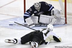 Penguins forward Evgeni Malkin gets a shot off while on his belly, but Jets goalie Ondrej Pavelec is equal to the task.