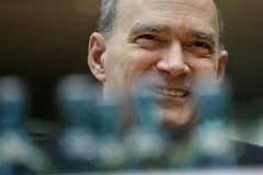 The former US National Security Agency, NSA, employee William Binney smiles behind water bottles as he waits for his questioning by the German parliamentary NSA investigation committee in Berlin, Germany, Thursday, July 3, 2014. The committee investigates the NSA surveillance activities, that also included the tapping of German Chancellor Angela Merkel. (AP Photo/Michael Sohn)