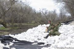 Members of 2nd battalion Princess Patricia's Canadian Light Infantry take a break from laying sandbags along a weak section of the dike running along the Assiniboine River, about 25 kilometres from Portage La Prairie on Thursday.