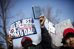 A demonstrator holds a bible while marching outside the Supreme Court in Washington, Tuesday, March 26, 2013, as the court heard arguments on California's voter approved ban on same-sex marriage, Proposition 8. The Supreme Court waded into the fight over same-sex marriage Tuesday, at a time when public opinion is shifting rapidly in favor of permitting gay and lesbian couples to wed, but 40 states don't allow it.